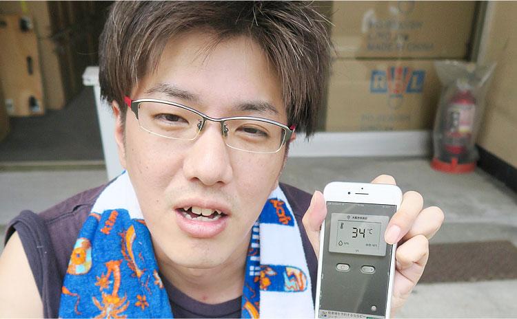 温度計を見せる男性スタッフ